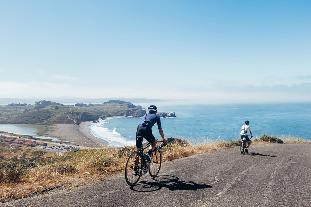 Group cycling overlooking ocean